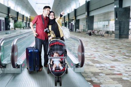 un couple en voyage avec leur bébé dans une poussette